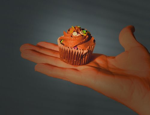A mini cupcake perched in the palm of a hand.