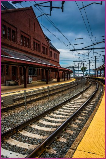 A railroad track curving around a red brick train depot