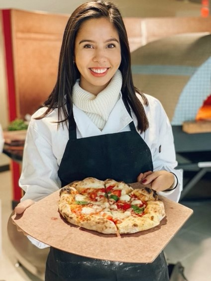 Young woman presenting a fresh pizza